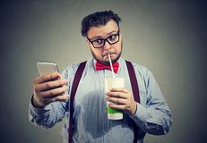 Addicted to sugar man drinking soda and using phone. Young chubby man addicted to social media and network using phone and drinking sweet soda Stock Photo