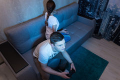 Addicted young man playing a video game and ignore his offended. Addicted young men playing a video game holding a console sitting on the sofa at home, ignore Royalty Free Stock Images