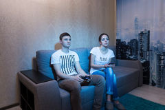 Addicted young man playing a video game sitting with his girlfri Royalty Free Stock Image