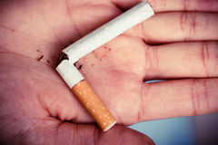 Addiction. Broken cigarette on hand. Quit smoking Stock Image