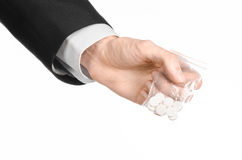 Addiction and business topic: hand in a black suit holds bag with white pills a drug on a white isolated background in studio Stock Image