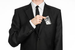 Addiction and business topic: hand in a black suit holds bag with white pills a drug on a white isolated background in studio Royalty Free Stock Photo