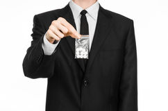 Addiction and business topic: hand in a black suit holds bag with white pills a drug on a white isolated background in studio Stock Photos