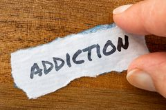Addiction concept and theme written on old paper on a grunge background royalty free stock photos