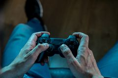 Close up of young mans hand holding a joystick in video game addiction concept. Addiction and dependency concept. close up on young mans hand with pad joystick royalty free stock image