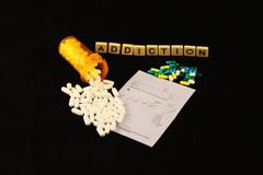 Addiction spelled out with tiles above spilled white pills over a prescription pad  black background. Addiction is spelled out in tiles. There is a spilled Stock Photos