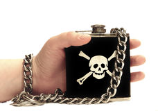 Addiction to alcohol. Hand holding drinking flask with skull on it. Hand and the flask are connected with massive chain stock image