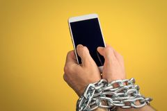 Addiction to smartphone or mobile devices concept. Iron chain that ties together hand and smart phone stock photos
