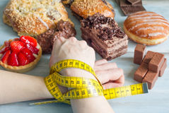 Addiction to sweets concept with woman's hand and centimeter Stock Images