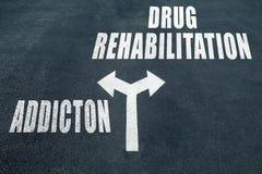Addiction vs drug rehabilitation choice concept. Two direction arrows on asphalt Royalty Free Stock Photography