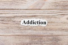 Addiction of the word on paper. concept. Words of Addiction on a wooden background royalty free stock image