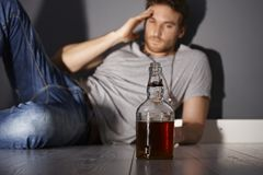 Addiction. Young addicted man with a bottle of whiskey Stock Photography