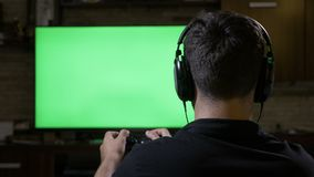 Addictive teenager wearing headphones chilling and playing video game using game controller on green screen TV at home -. Addictive teenager wearing headphones stock footage