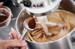 Addieren des Kakaopulvers Lizenzfreie Stockfotos
