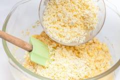 Addieren des zerrissenen Käses, um Zuckermaisbrot zuzubereiten Stockfotografie