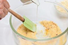 Addieren von Milch, um Zuckermaisbrot zuzubereiten Stockfoto
