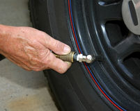Adding air to an automobile tire. Service man adding air to an automobile tire to increase mileage and safety Royalty Free Stock Photography