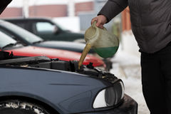 Adding antifreeze. Near garage in winter stock images