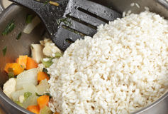 Adding arborio rice. Adding arborio (italian risotto) rice to a bowl of frying chicken, onion, carrot and celery Stock Photo