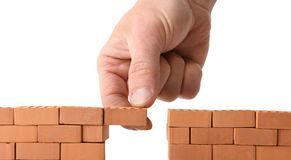 Adding brick to a gap in the wall Stock Photos