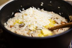 Adding butter and parmigiana in a risotto dish Royalty Free Stock Photography