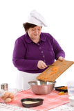 Adding the carrots. Female chef putting the carrots in the bowl Royalty Free Stock Photography