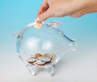 Adding a coin. Hand adding a dollar to a glass piggy bank Stock Photos