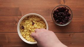 Adding cranberries into bowl with cereal flakes. Adding cranberries into bowl with cereal flakes, healthy breakfast. Overhead shot stock video