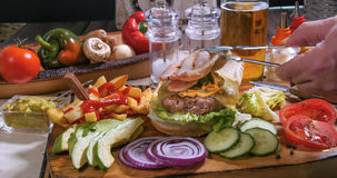 Adding crispy bacon over a cheesburger with beer and French fries Stock Photos