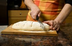 Adding cut to unbaked bread dough Royalty Free Stock Photos