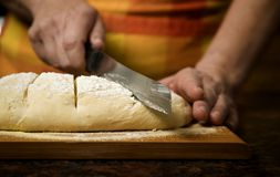 Adding cut to unbaked bread dough Royalty Free Stock Images