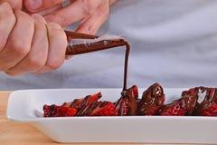 Adding dark chocolate cream on strawberries. Royalty Free Stock Photos