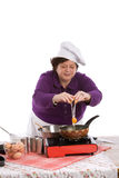 Adding an egg. Female chef breaking an egg above her pan Royalty Free Stock Photography