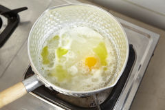 Adding egg. To the boiled stock soup Stock Photo