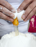 Adding egg to flour Royalty Free Stock Photography