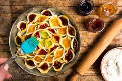 Adding egg yolk to homemade sweet pie with various fruit. Jams stock image