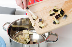 Adding eggplant pieces into saucepan Stock Images