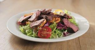 Adding fillet mignon steak into salad. Wide photo stock photo