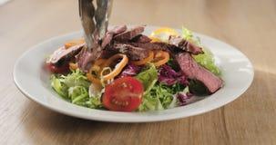 Adding fillet mignon steak into salad. Wide photo royalty free stock photo