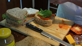 Adding fresh lettuce to sandwiches at Mac's pizzeria stock footage