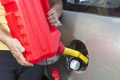Adding fuel in car with Red Plastic Gas can. (fuel container royalty free stock photography