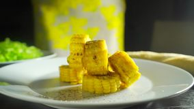 Adding ground pepper and salt to roasted corn cob pieces, 2 videos in 1 stock video