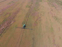 Adding herbicide tractor on the field of ripe wheat. View from above. Adding herbicide tractor on the field of ripe wheat. Growing crops in the fields. View Stock Image