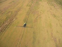 Adding herbicide tractor on the field of ripe wheat. View from above. Stock Image