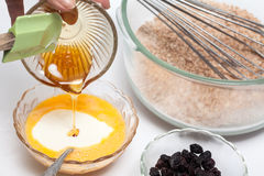 Adding honey to the mix to prepare integral wheat bran muffins Stock Photos