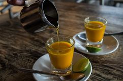 Adding honey to two healthy jamu shots in close-up Stock Images