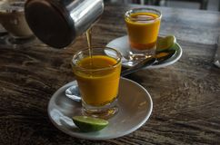 Adding honey to two healthy jamu shots in close-up without hand different perspective Stock Photos