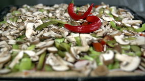 Adding hot peppers over the pizza. Adding various pizza ingredients all over the dough stock video footage