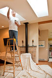 Adding Interior Skylights. Man adding finishing touches to newly installed interior home skylights Stock Images