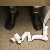 Adding machine printout at feet of retro business man. stock photo